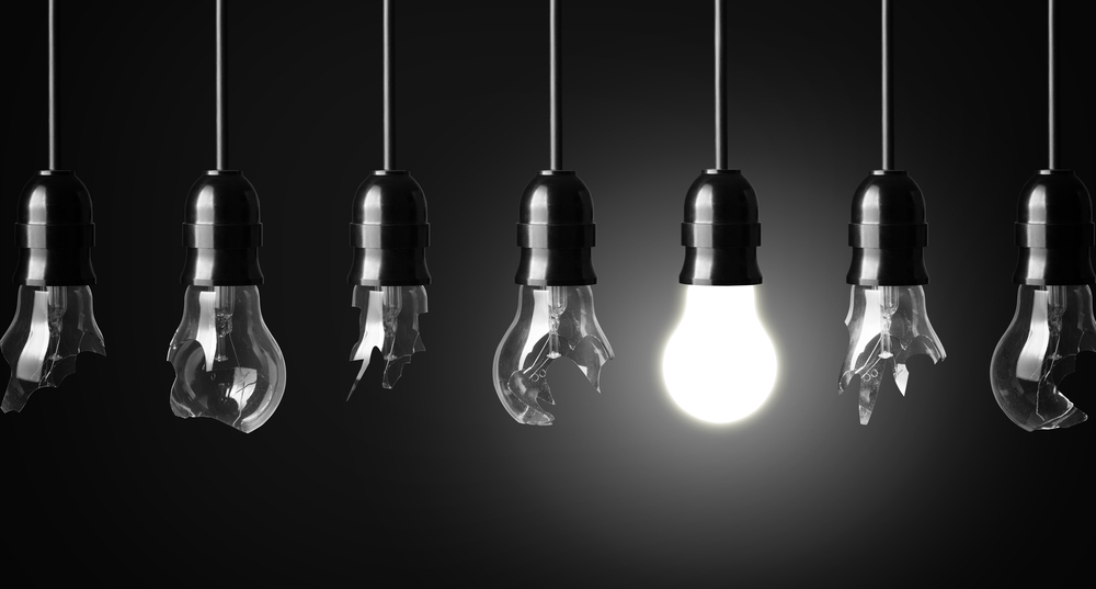 Black and white image of hanging lightbulbs, only one is lit